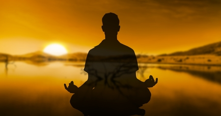 Digital composite of Double exposure of person meditating with lake in background during sunset