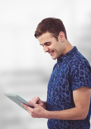 Digital composite of Smiling young man using tablet PC