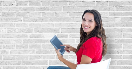 Digital composite of Smiling woman using tablet PC against wall