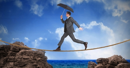 Digital composite of Businessman with umbrella walking on rope