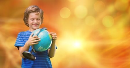applauding: Digital composite of Smiling boy looking at globe over bokeh Stock Photo