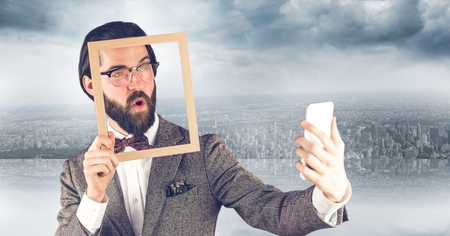 Digital composite of Hipster holding frame while taking selfie on mobile phone