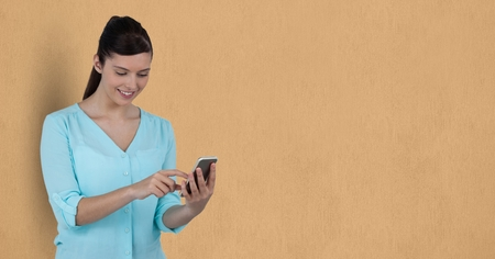 woman cellphone: Digital composite of Businesswoman using mobile phone over beige background
