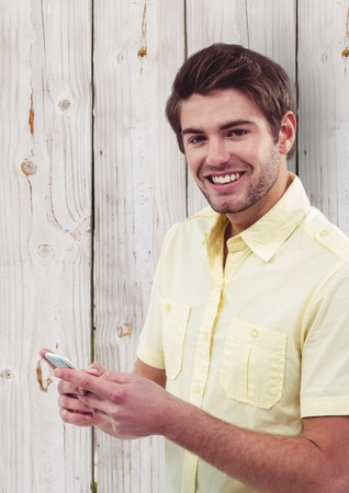 man holding transparent: Digital composite of Portrait of happy male hipster holding smart phone against wooden wall