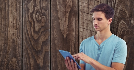 panelling: Digital composite of Young man using tablet PC against wall