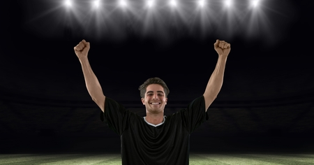 Digital composite of Successful soccer player with arms raised at stadium 版權商用圖片