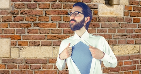 tied down: Digital composite of Hipster tearing shirt against brick wall Stock Photo