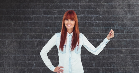 cross legged: Digital composite of Redhead businesswoman gesturing against wall