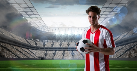 Digital composite of Soccer player holding ball at stadium