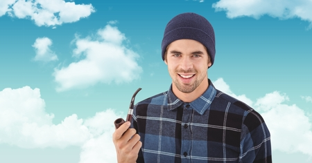 Digital composite of Smiling hipster holding smoking pipe against sky Stock Photo
