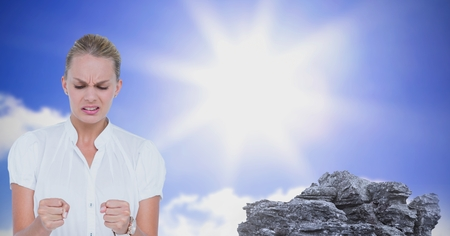 Digital composite of Angry businesswoman by rock against sun Stock Photo