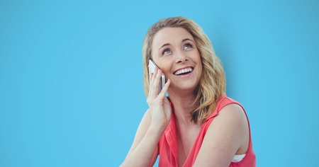phoning: Digital composite of Happy female hipster using smart phone against blue background