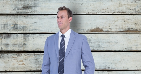 Digital composite of Thoughtful businessman standing against wooden wall
