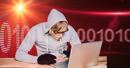 Digital composite of Hacker using laptop with binary code in background