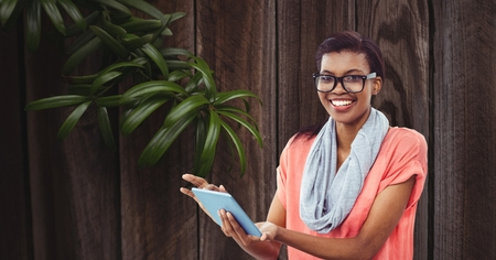 using tablet: Digital composite of Smiling businesswoman using tablet PC against wall Stock Photo