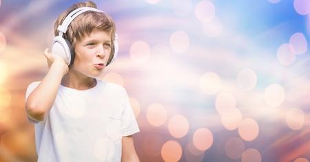 Digital composite of Excited boy listening music through headphones over bokeh