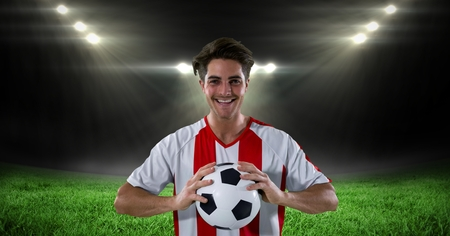 Digital composite of Happy player holding soccer ball