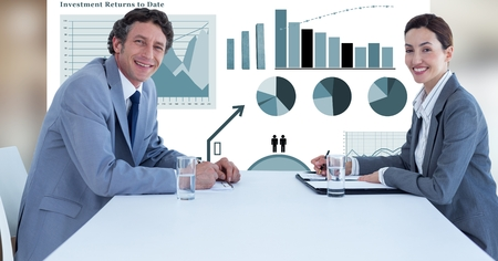 Digital composite of Smiling business people at desk against graphs Stock Photo