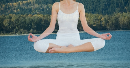 Digital composite of Double exposure of woman meditating over lake