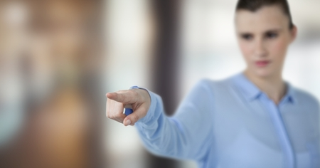 futuristic interior: Digital composite of Businesswoman pointing over blurred background Stock Photo
