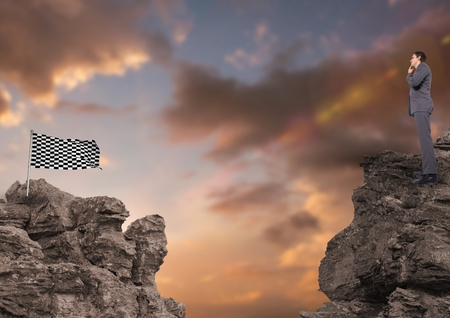 Digital composite of Business person and checked flag on rocks against sky