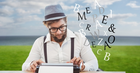 Digital composite of Hipster using typewriter while letters flying Stock Photo