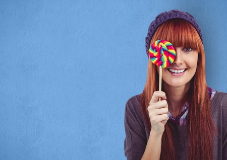 Digital composite of Happy female hipster covering eye with candy against blue background