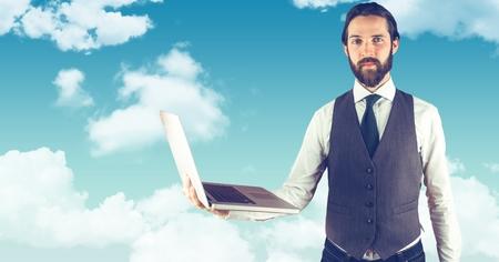 Digital composite of Hipster holding laptop against sky