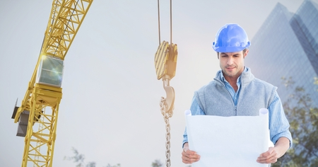 Digital composite of Architect holding blueprint against crane Stock Photo