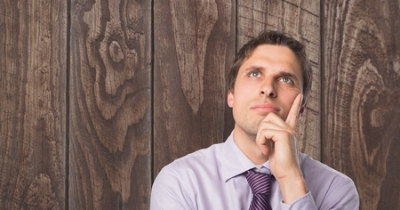 Digital composite of Thoughtful businessman with hand on chin against wooden wall Stock Photo
