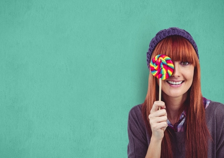 Digital composite of Portrait of female hipster covering eye with candy against green background