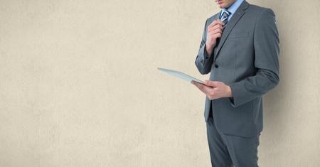 Compuesto digital del Midsection del hombre de negocios que sostiene la tableta digital sobre fondo coloreado Foto de archivo