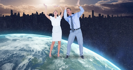 Digital composite of Business people with arms raised on globe