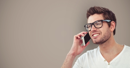 Digital composite of Male hipster using smart phone against brown background