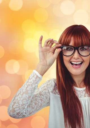 Digital composite of Cheerful female hipster wearing eyeglasses over bokeh Stock Photo