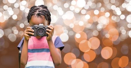 Digital composite of Boy photographing through camera over bokeh