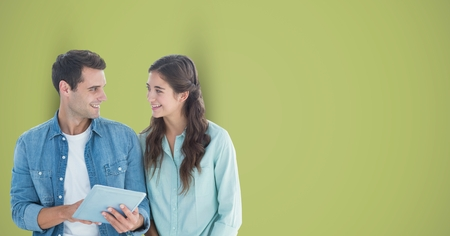 Digital composite of Male and female hipsters with digital tablet against green background Stock Photo