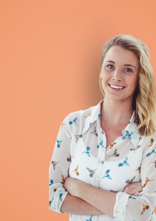 Digital composite of Portrait of casual businesswoman standing arms crossed against orange background