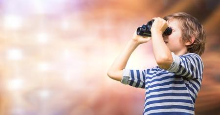 Digital composite of Boy looking through binoculars over blur background 版權商用圖片