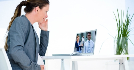 Digital composite of Businesswoman video conferencing with partners on computer