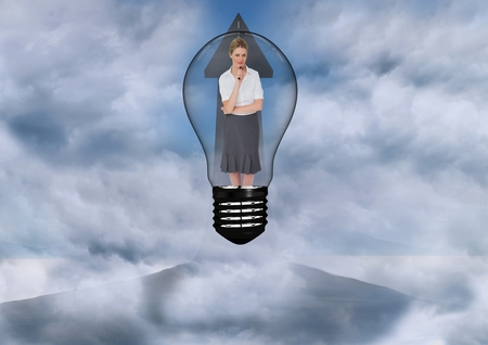 Digital composite of Businesswoman standing in bulb against sky Stock Photo