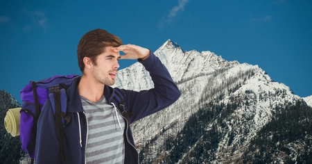 Digital composite of Male traveler shielding eyes while carrying backpack on mountain