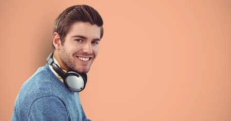 Digital composite of Smiling male hipster with headphones against orange background Stock Photo