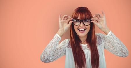 Digital composite of Cheerful redheaded female hipster wearing eyeglasses against orange background