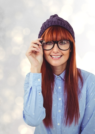 Digital composite of Portrait of happy redheaded female hipster wearing eyeglasses and knit hat Stock Photo