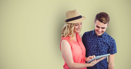using tablet: Digital composite of Male and female hipsters using digital tablet against green background Stock Photo