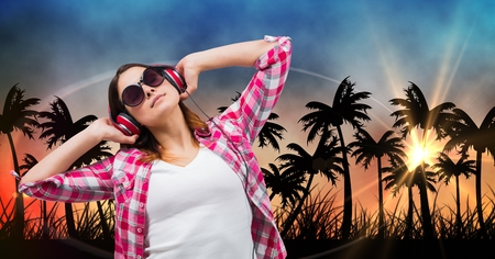 met: Digital composite of Beautiful woman listening music through headphones while standing against silhouette trees