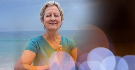 Digital composite of Senior women meditating on beach against sky Banco de Imagens