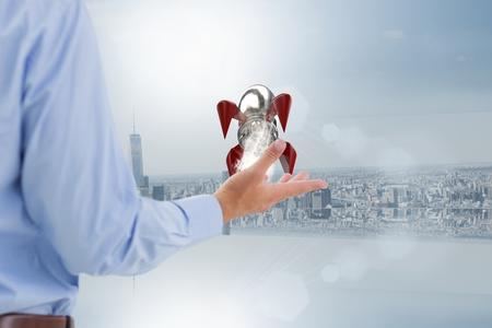 Digital composite of Business man holding a rocket on his hand