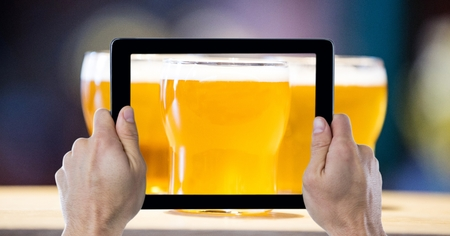camaraderie: Digital composite of Cropped hands photographing beer glasses through digital tablet at bar